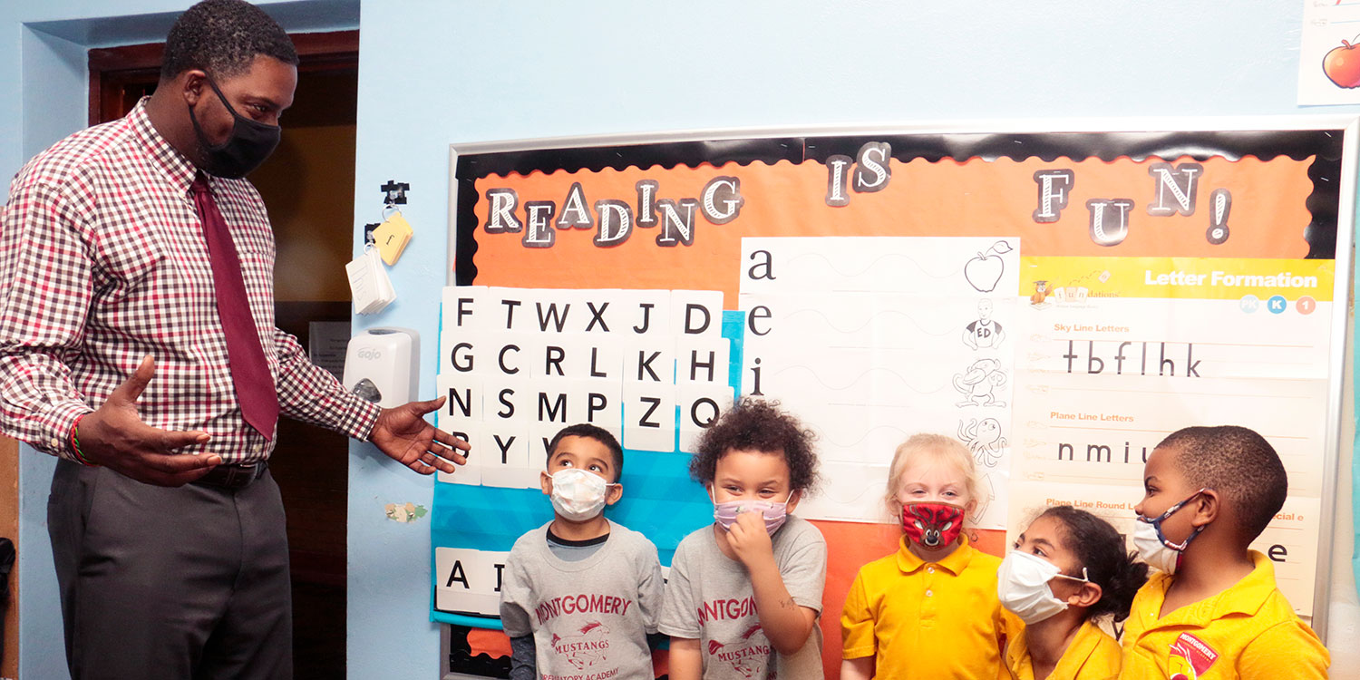 Masked elementary students standing by bulletin board.