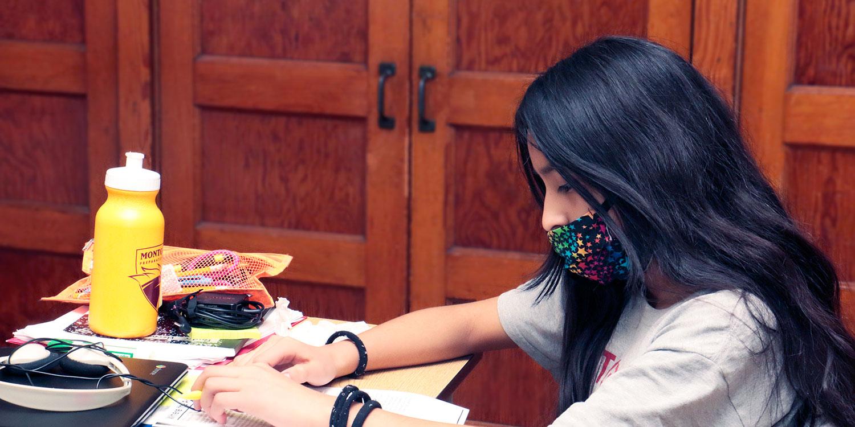 Masked student at a desk.