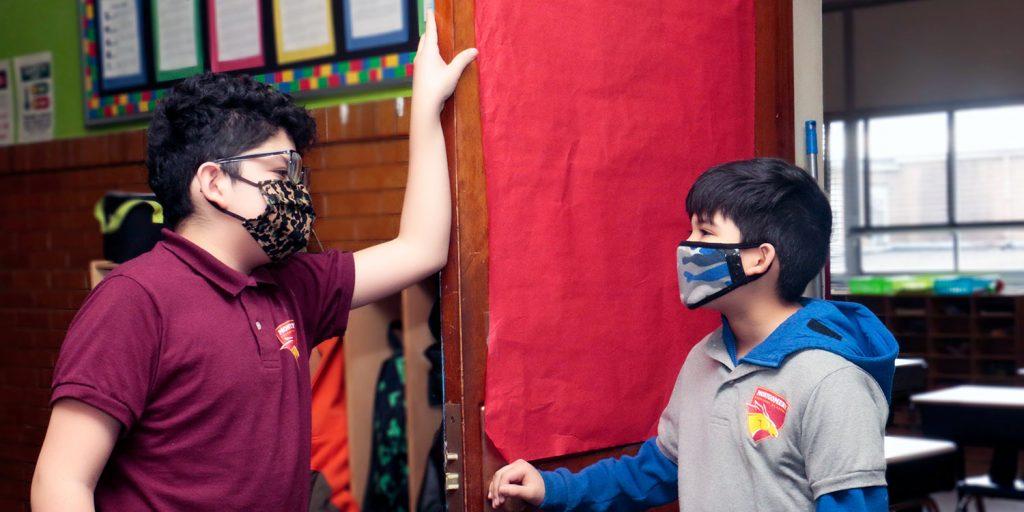 Masked students talking in hallway.