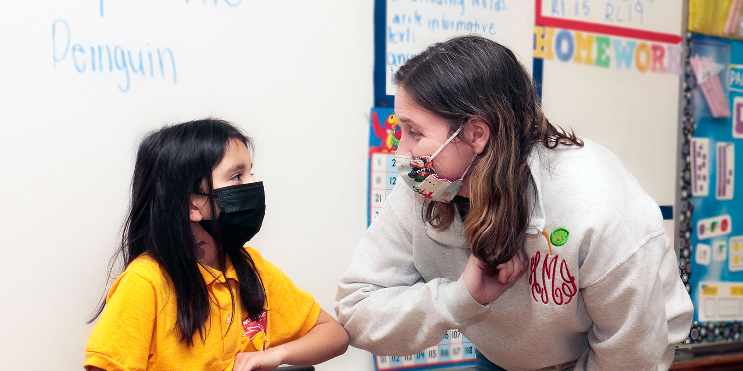 Masked student and teacher touching elbows.