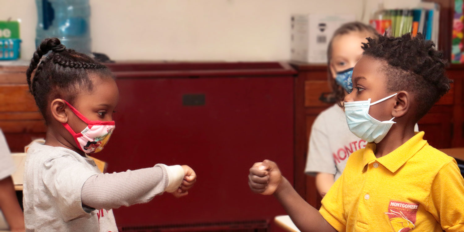 Masked students limiting contact with a fist bump.